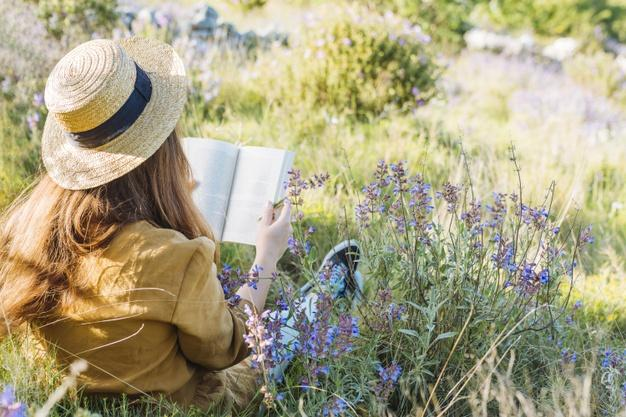 woman-reading-a-book-in-nature-surrounded-by-vegetation-and-flowers_23-2148568385
